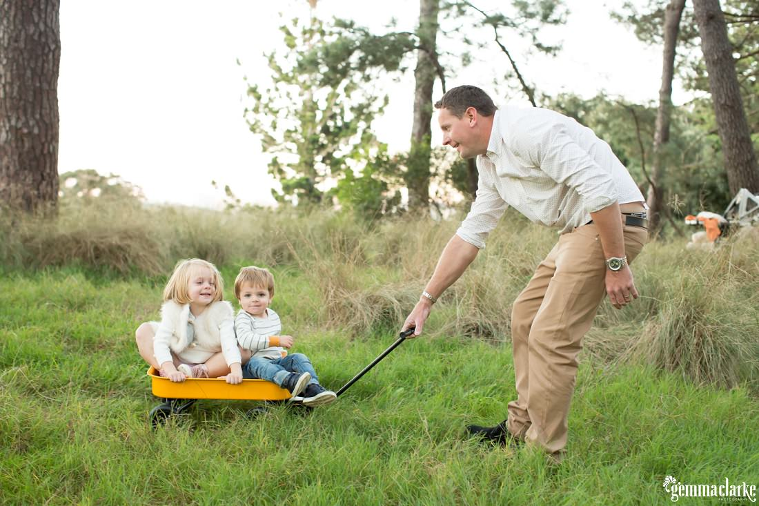 A father pulls his son and daughter in a small cart