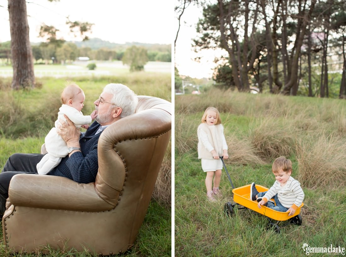 A grandfather sits in a leather armchair holding his baby granddaughter, and a young girl pulls her younger brother along in a cart