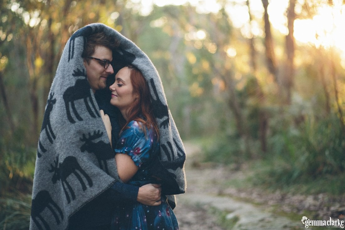 A man and woman embrace while wrapped in a blanket - Bush Engagement Photos