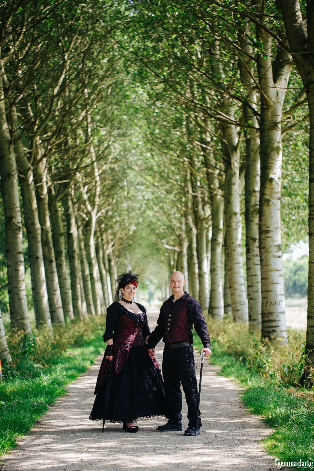 A row of trees and a bride and groom standing in between them with their black and red attire for this Friday the 13th Wedding