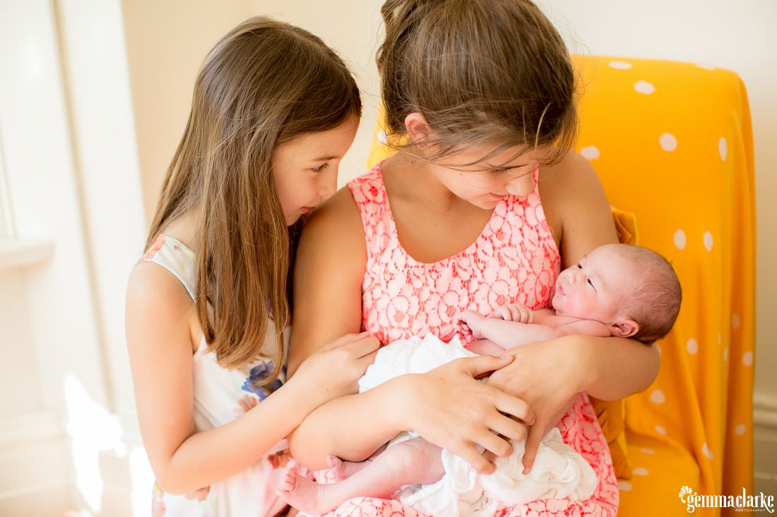 Two young sisters holding their newborn baby brother - Relaxed Newborn Portraits