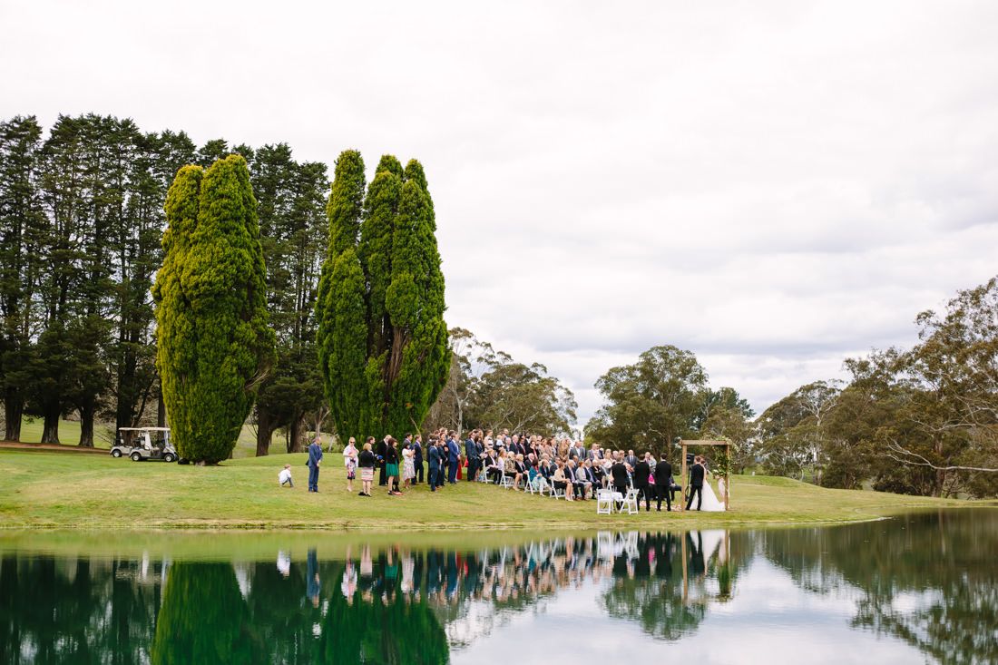 An overall view of the ceremony with guests and bridal party standing by a lake with the reflections and many trees around. The day is overcast at this Gibraltar Hotel Wedding.