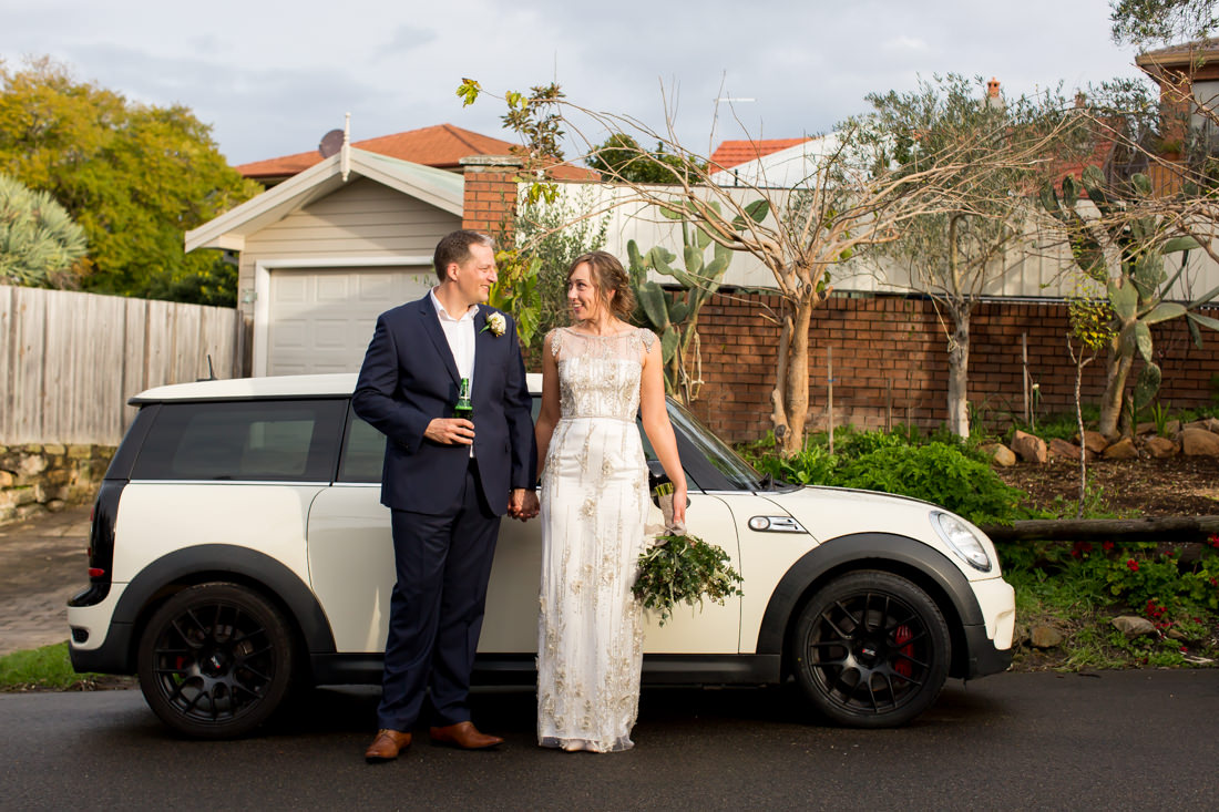 Couple standing in wedding attire in front of a beige Mini Countryman car