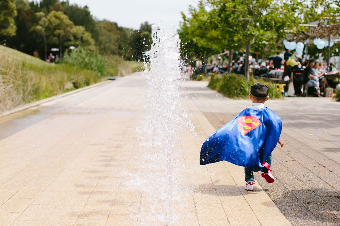 A small boy running away from the camera with his superman cape flying in the wind and a big fountain to his left.