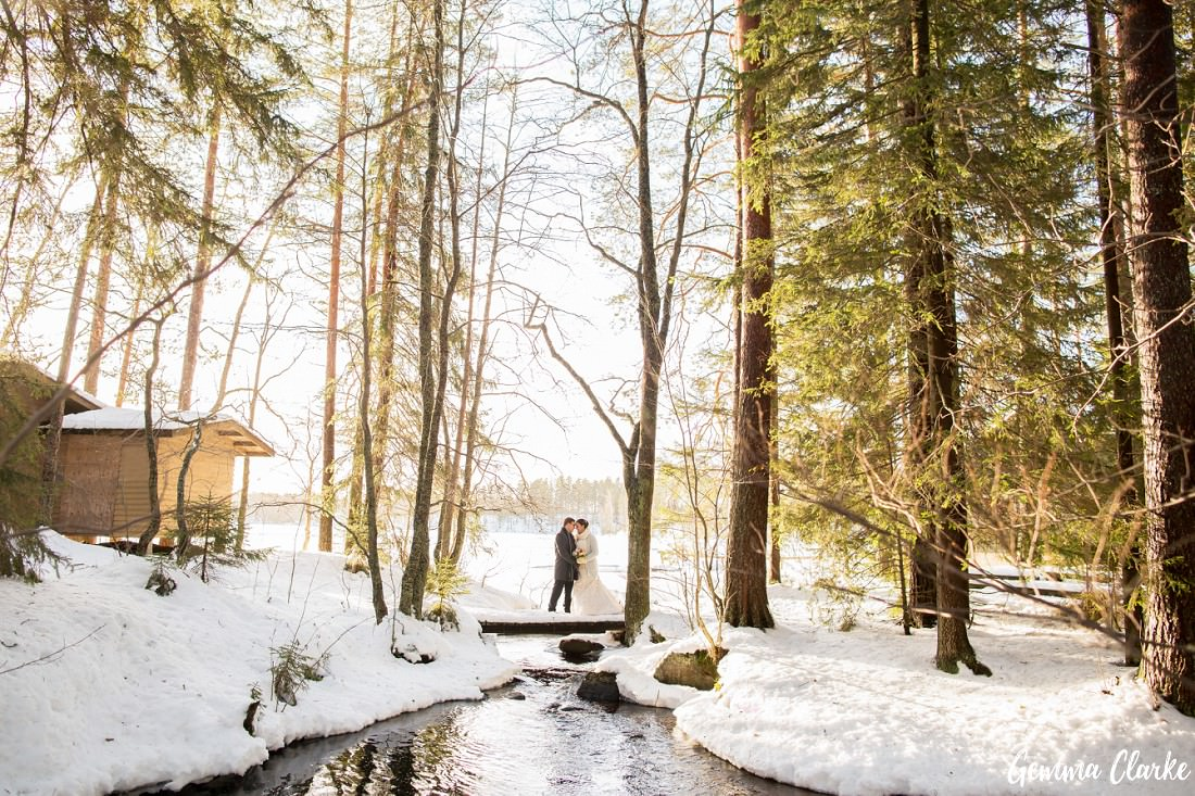 Couple standing on snowy bridge in the forest with the sun shining on them - 2016 Highlights