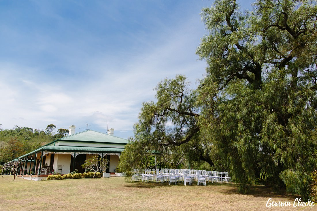 View of the Pepper Tree Ridge Wedding homestead and ceremony setup with massive tree and blue sky in country setting