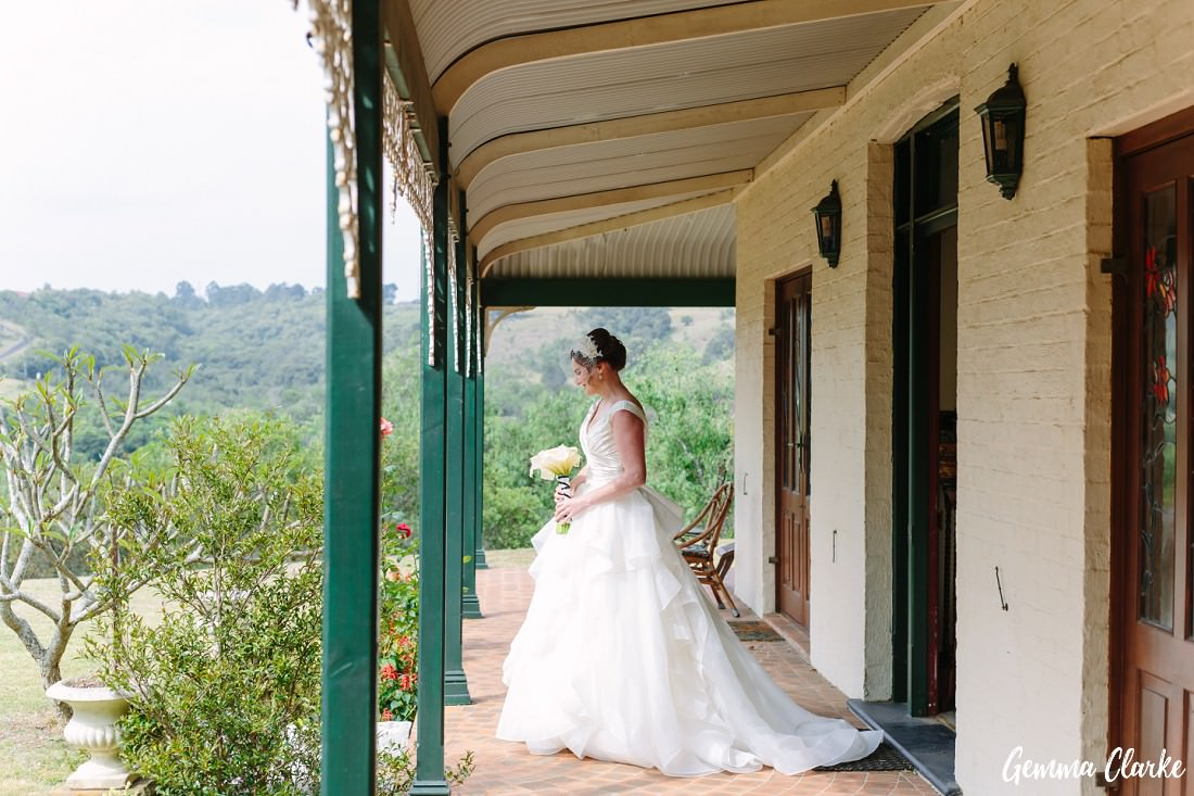 Bride walks out onto verandah at the top of the wedding aisle. Her long white dress is flowing out the back at this Pepper Tree Ridge Wedding