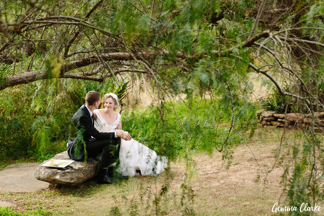 Bride and Groom sitting on a rock looking at each other. Seen through an overhanging tree at this Pepper Tree Ridge Wedding