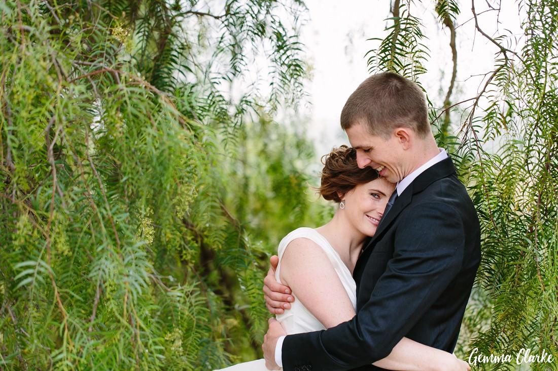 Bride and Groom cuddling among the leaves of the overhanging tree and bride looking cheeky at this Pepper Tree Ridge Wedding