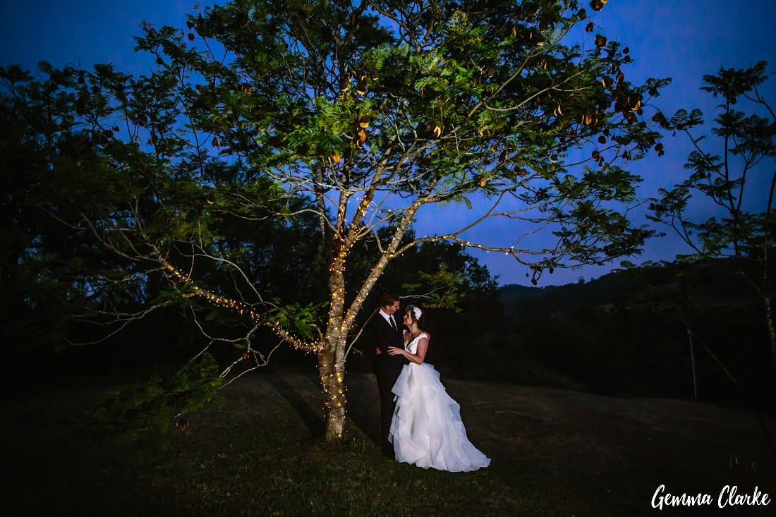 Night time under a fairy light lit tree and a big beautiful blue sky with the bride and groom underneath at this Pepper Tree Ridge Wedding