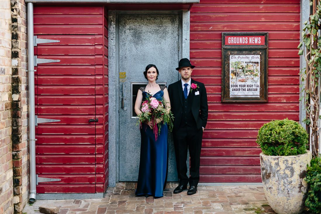 Bride and Groom looking grungy standing against a rustic red wall in the Grounds of Alexandria