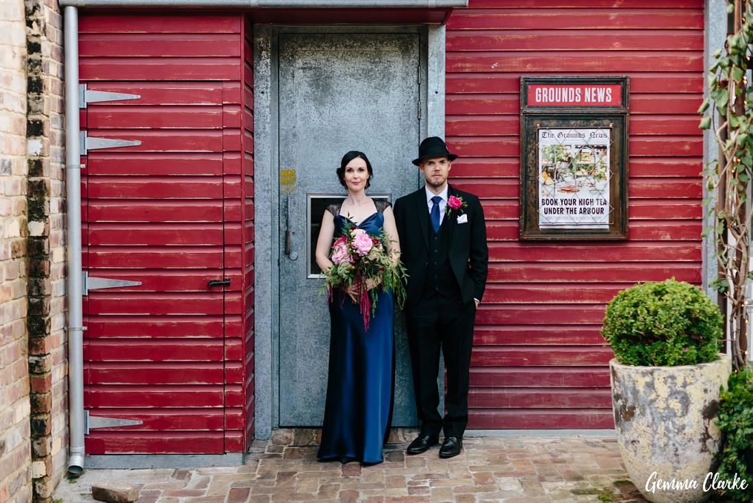 Bride and Groom stand by a red rustic wall at this Grounds of Alexandria Wedding. Bride is in a blue dress and groom is in a cool black hat.