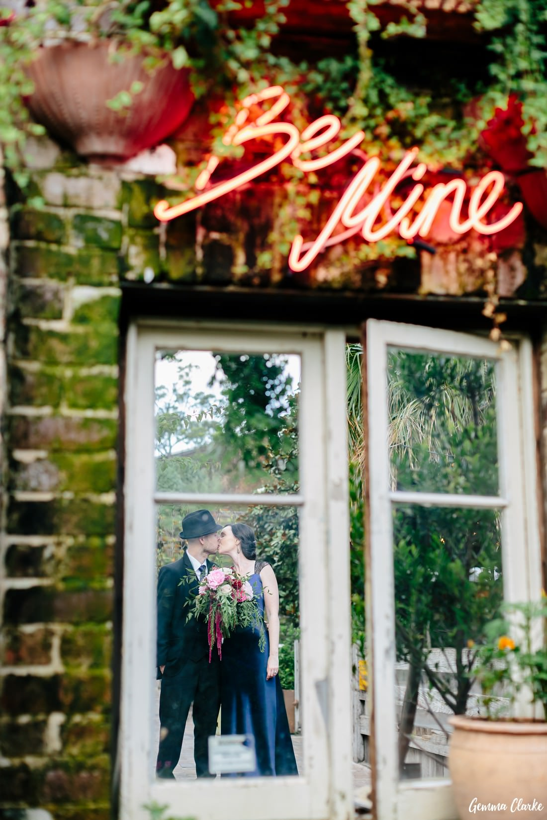 Bride and Groom kissing from behind a window and with an illuminated sign saying Be Mine above them at this Grounds of Alexandria Wedding