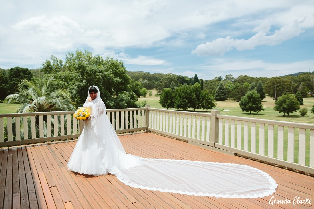 Bride with long four metre veil stands on decking overlooking the golf course at this Peppers Craigieburn Wedding