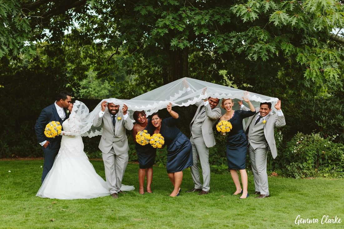 A fun moment with the bridal party hiding under the bride's long four metre lace veil at this Peppers Craigieburn wedding
