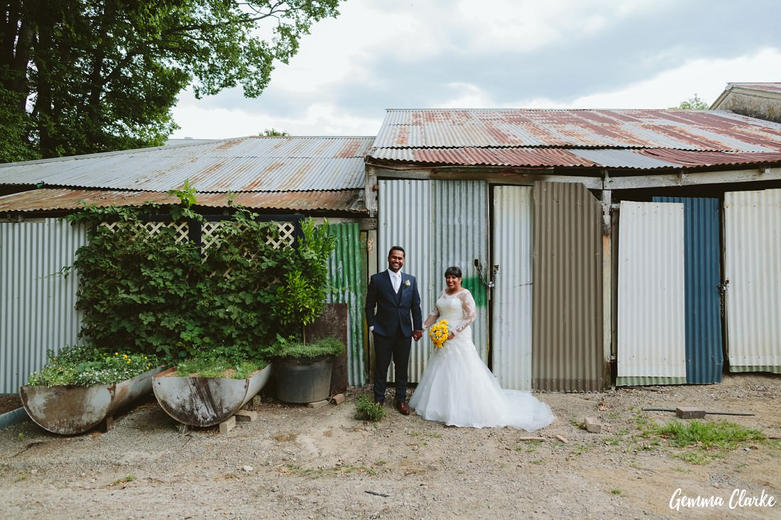 Bride and Groom holding hands in front of old rustic sheds and a vegetable garden at this Peppers Craigieburn Wedding