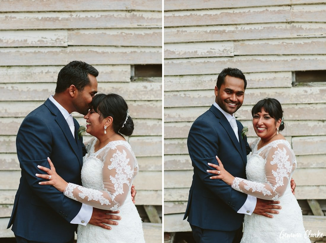 Groom kisses the forehead of the bride and also smiles at the camera in front of a rustic building at this Peppers Craigieburn Wedding