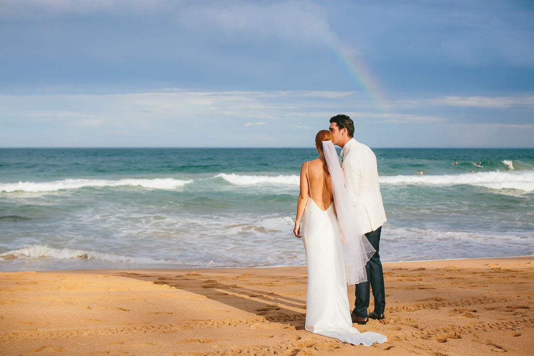Bride and Groom standing on a beach looking out to the water with a rainbow in the distance at this Whale Beach Wedding.