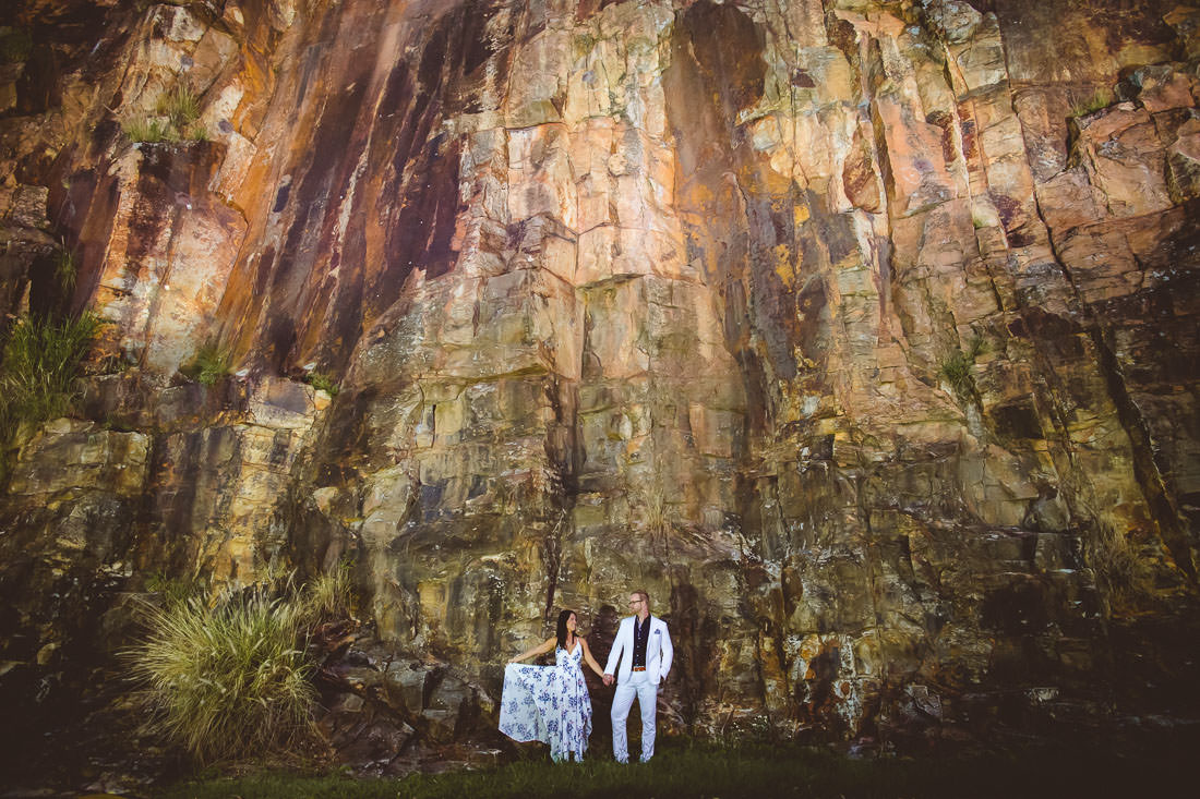 Couple dressed in white holding hands in front of a big cliff