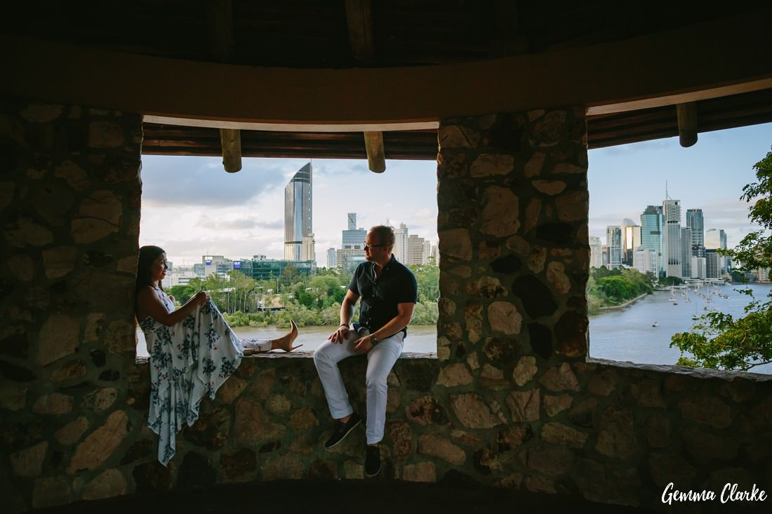 Couple sit on the ledge of a stone gazebo that overlooks Brisbane City and the river at Kangaroo Point