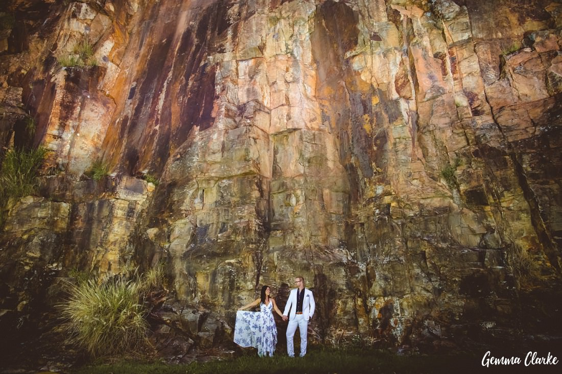 Couple in white clothing are holding hands and standing in front of a large rocky cliff at Kangaroo Point for their Engagement Photos
