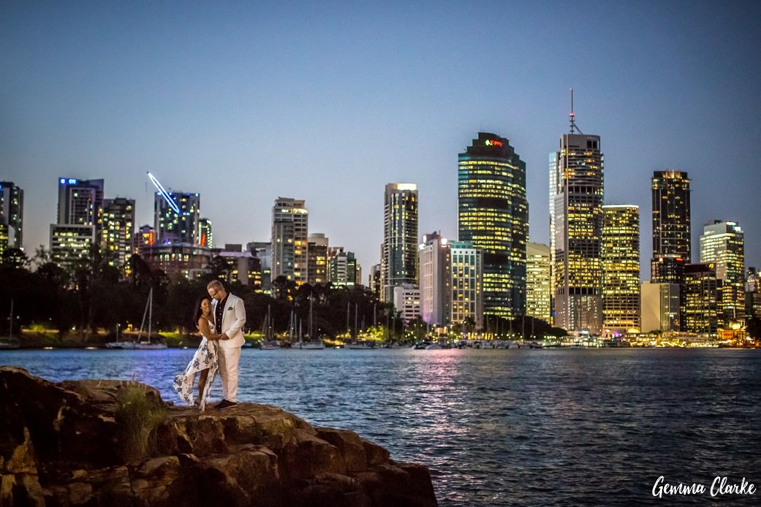 A couple cuddle on a rocky outcrop at night with the lit up Brisbane City in the background at Kangaroo Point for their engagement