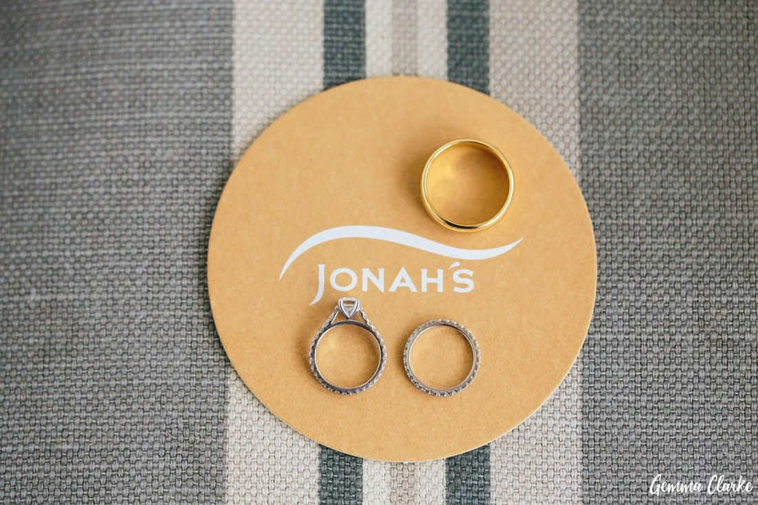 The wedding rings and engagement ring placed on Jonahs Whale Beach coaster at this Whale Beach Wedding