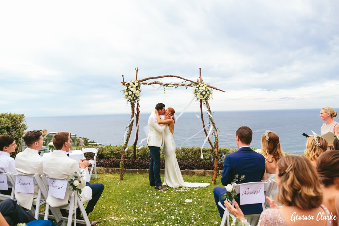 THe kiss during the ceremony in front of an ocean backdrop and a floral arbour at this Whale Beach Wedding