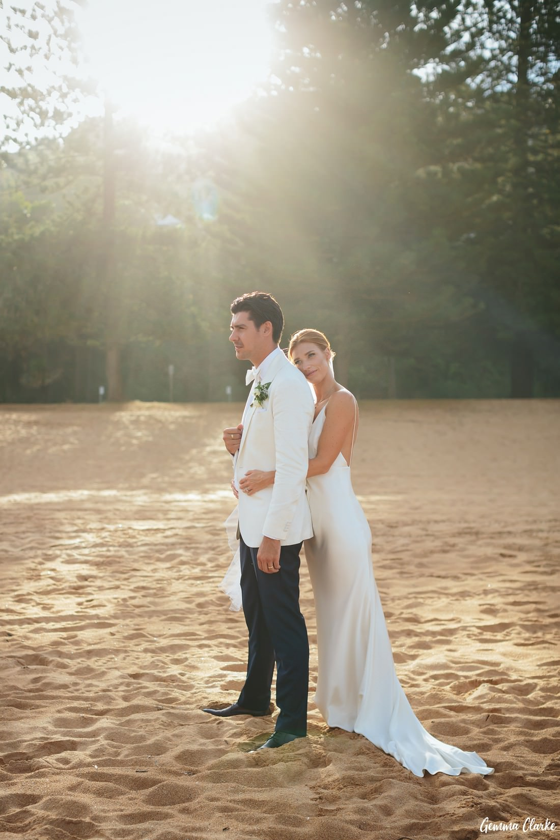 Bride and groom cuddle on the beach with the sun streaming in through the trees at this Whale Beach Wedding