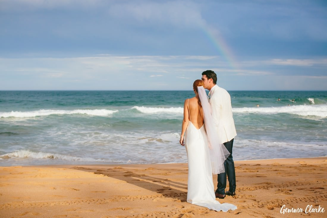 Bride and Groom kiss on the beach with a rainbow in the distance at this Whale Beach Wedding