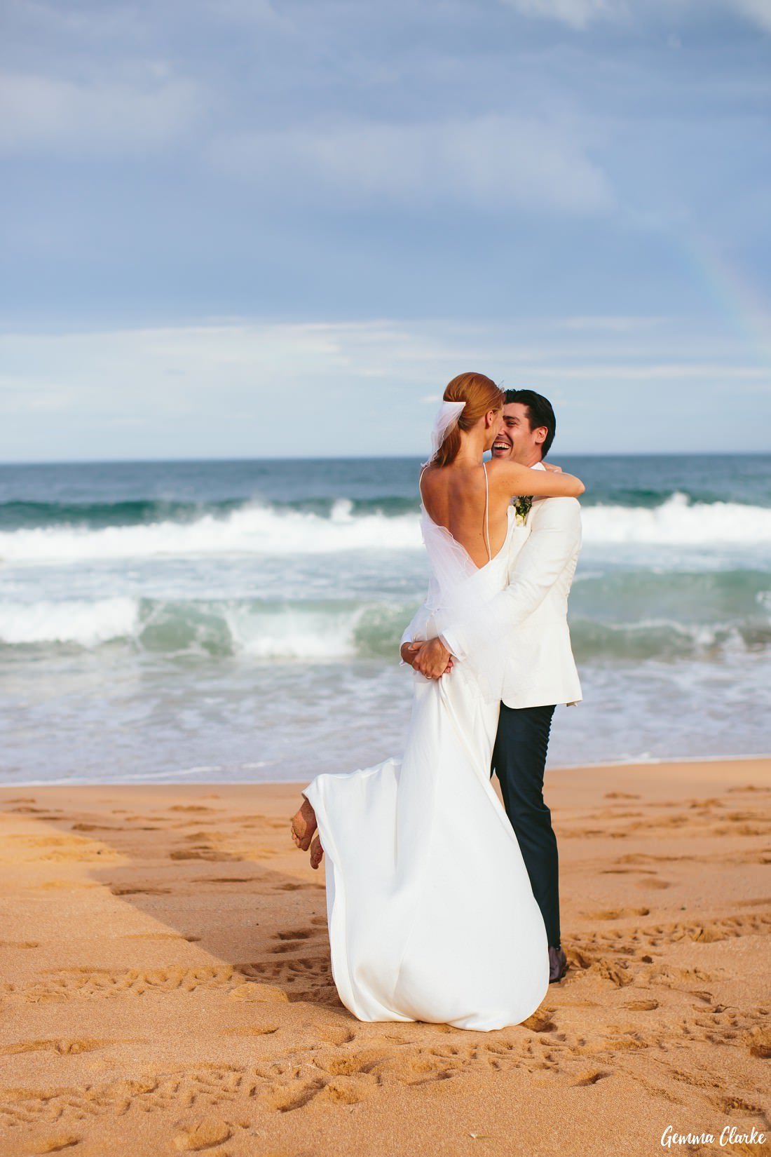 Bride is picked up by the groom and they embrace on the beach with a fading rainbow in the distance at this Whale Beach Wedding