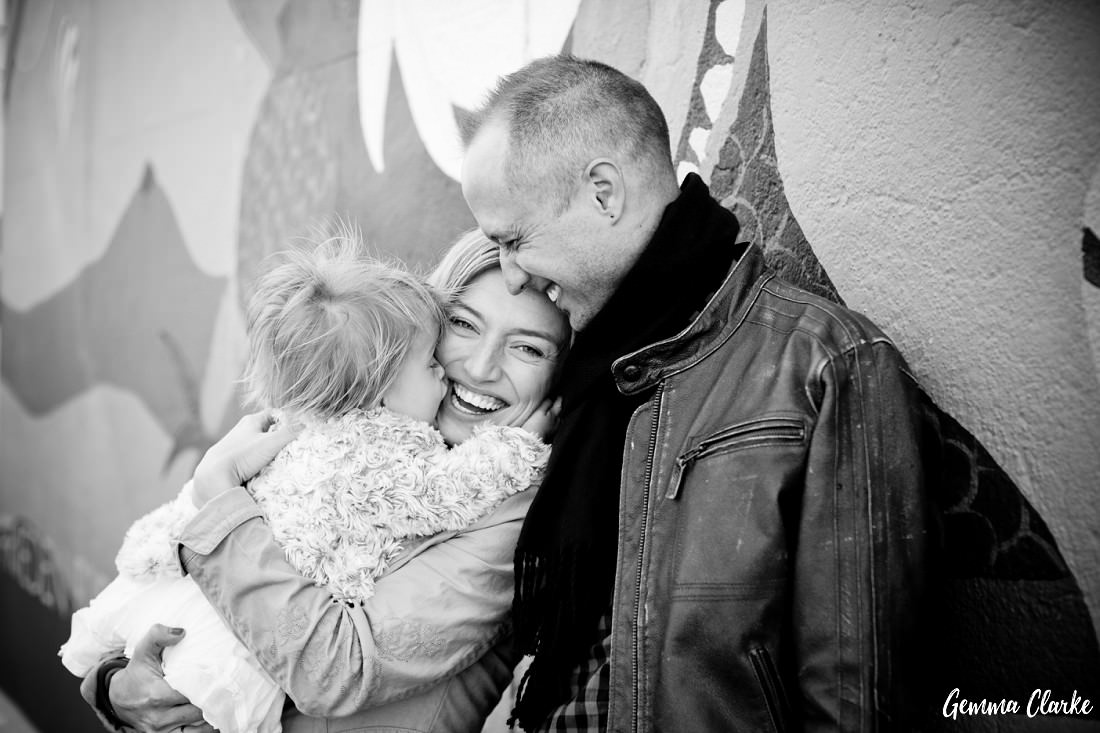 Toddler kisses her mum's cheek while Dad cuddles mum and there are smiles all around at the East Side Gallery in these Lifestyle Portraits in Berlin