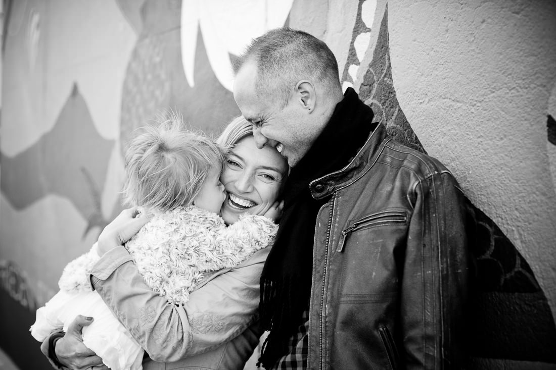 Berlin Lifestyle Portraits - Family of three cuddling in front of the East Side Gallery