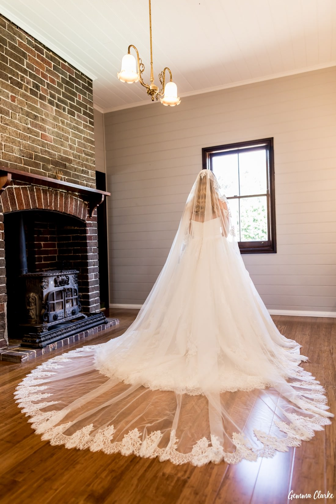 Bride with her long lace trimmed veil facing away and there is an old fireplace to her left at this Burnham Grove Estate Wedding