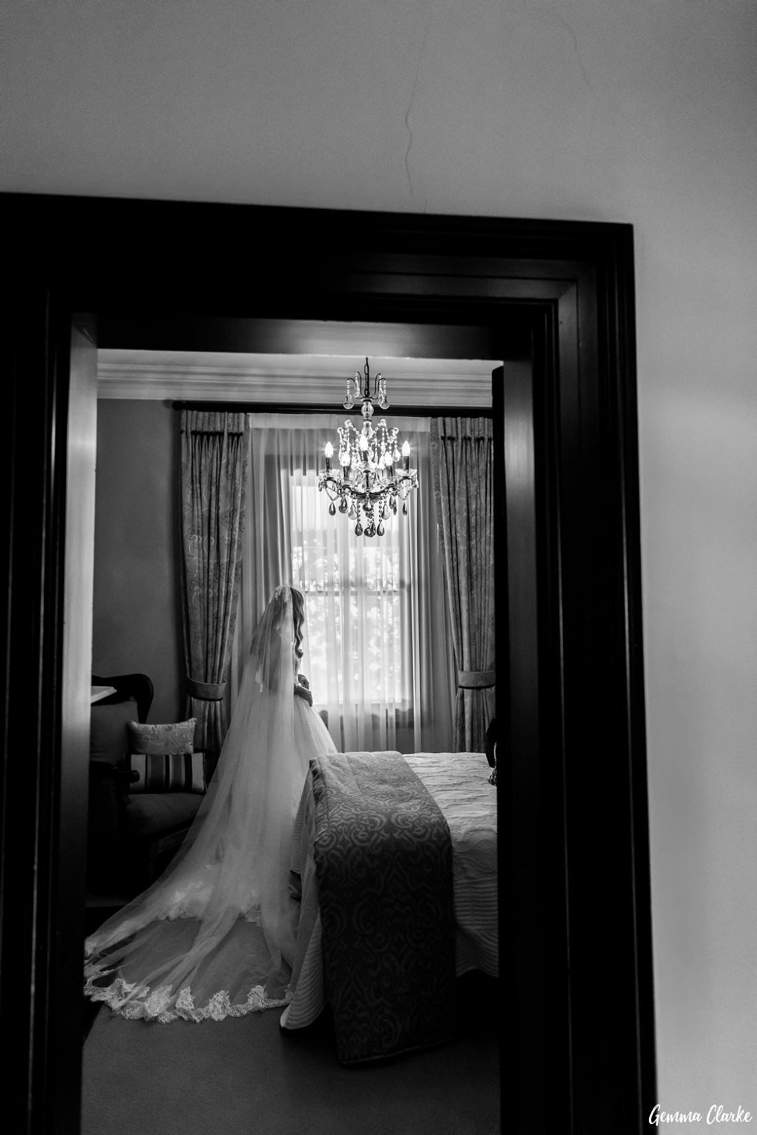 Bride in a luxurious bedroom looking out the window with stunning window dressing and a chandelier hanging from the ceiling at this Burnham Grove Estate wedding