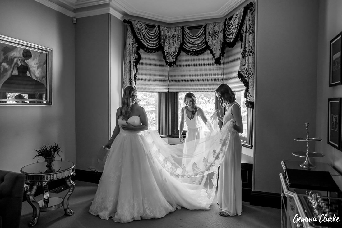 Bridesmaids try to fix the bride's big dress and veil in a gorgeous room with stunning window dressings at this Burnham Grove Estate Wedding