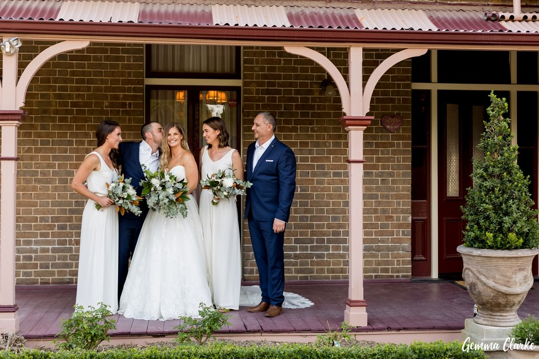 Bridal party on the front of the verandah of a country homestead at this Burnham Grove Estate wedding