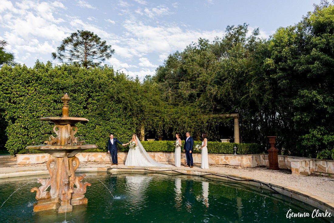 Bridal party walk around the fountain area with gorgeous lush green gardens surrounding the pool area at this Burnham Grove Estate wedding