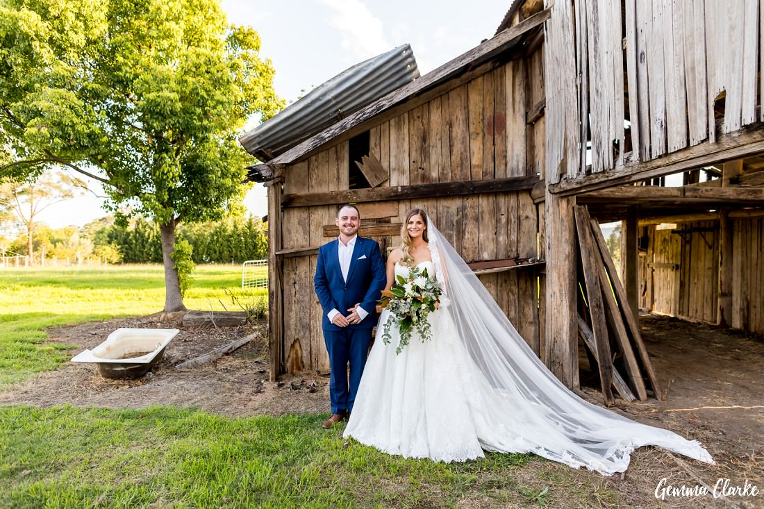 Bride and groom standing in front of a heritage barn with an old bath to the side at this Burnham Grove Estate wedding