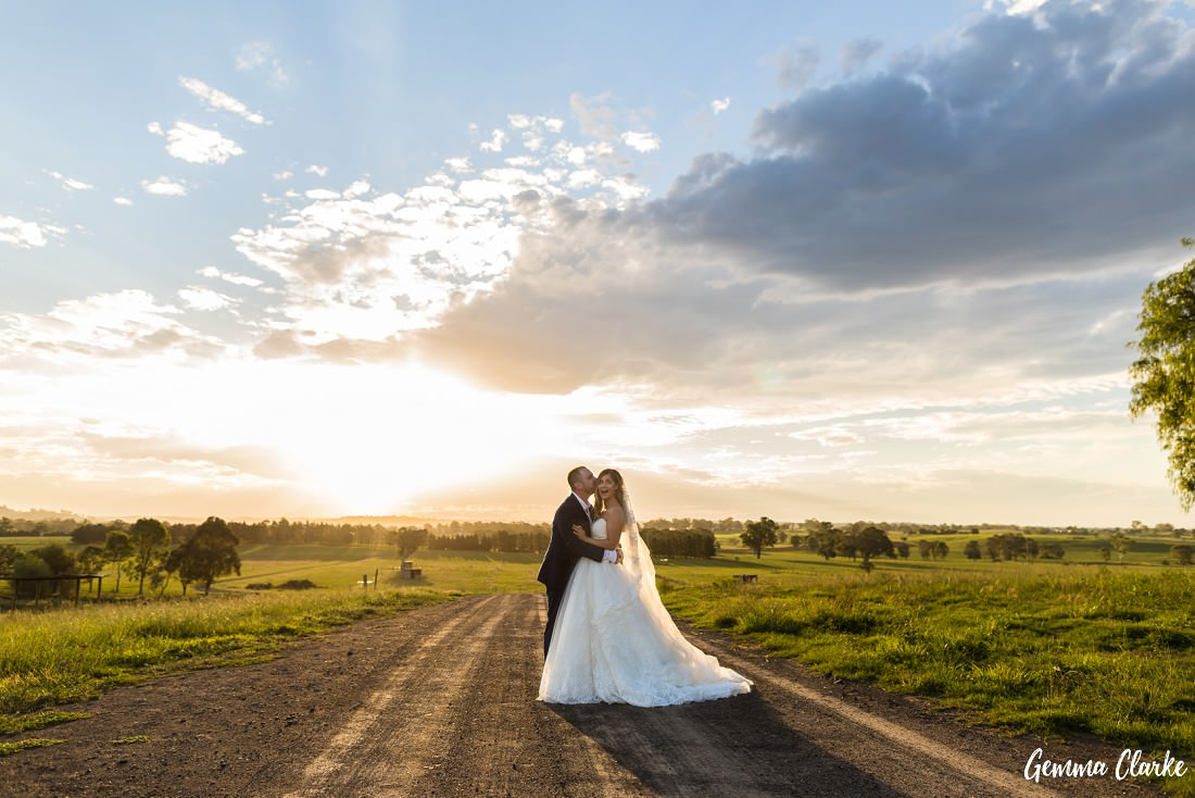 Lots of fun as the groom kisses the bride on the side of the head and makes her laugh as we see the gorgeous sun setting in the country background at this Burnham Grove Estate wedding