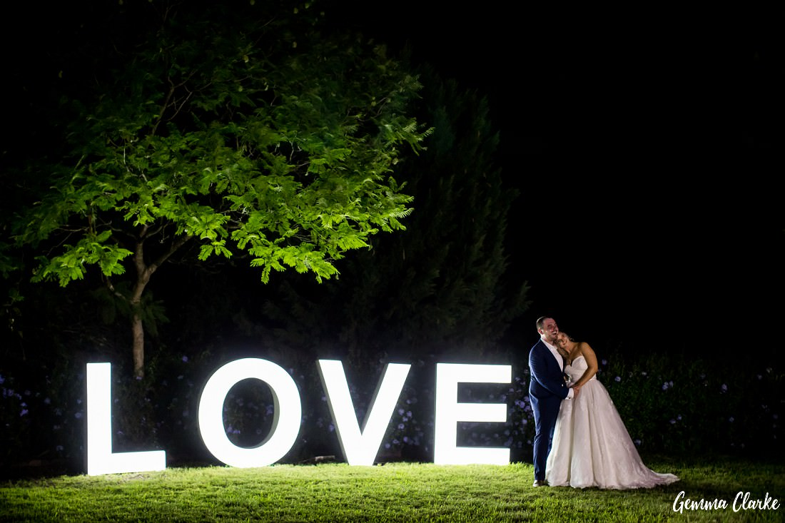 At night, the bride and groom are snuggling next to big illuminated letters spelling out the word LOVE at this Burnham Grove Estate Wedding