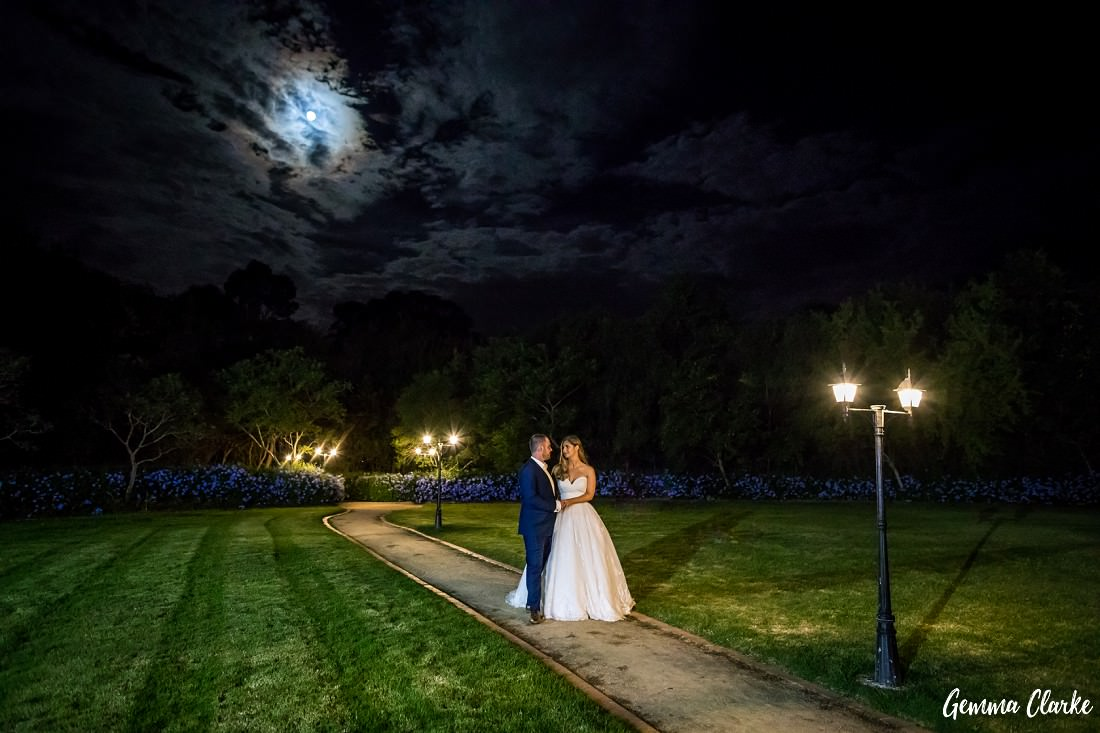 At night, the bride and groom stand on a path in amongst the garden with lanterns lits and the moon peeking through the clouds at this Burnham Grove Estate wedding
