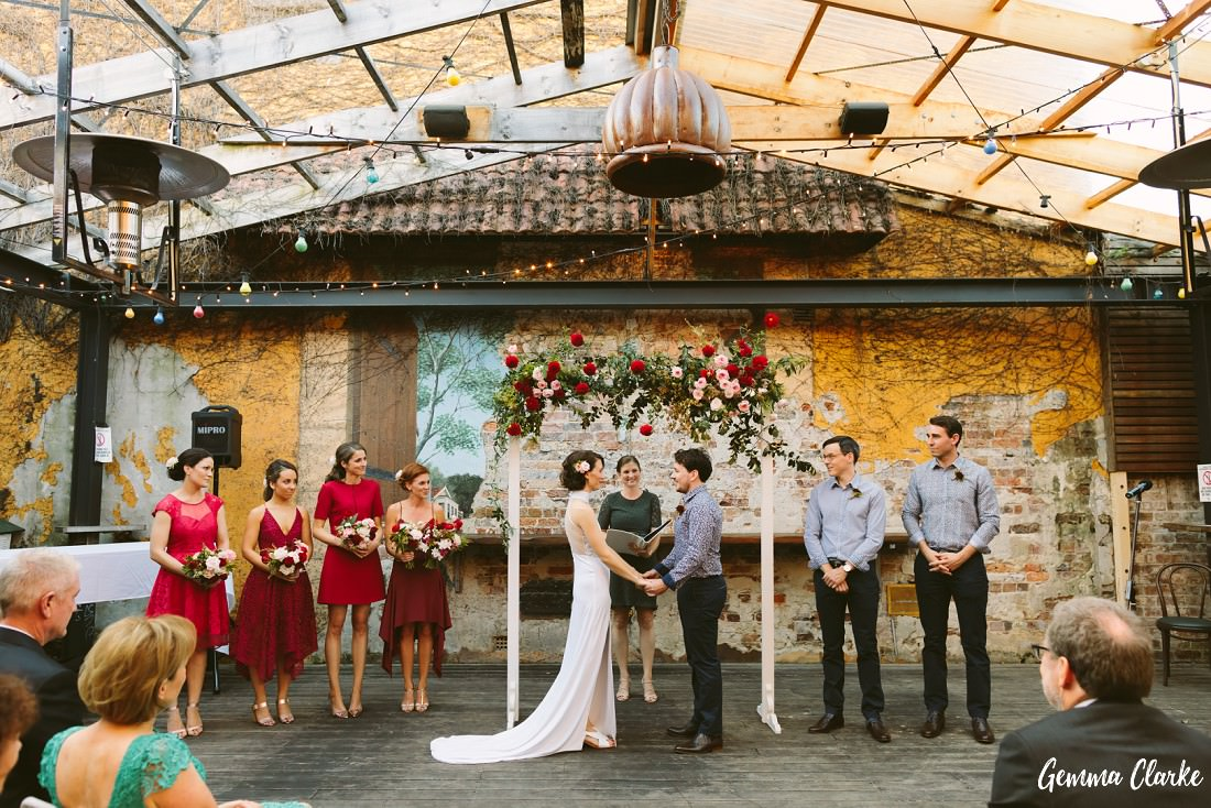 Bridal Party during the wedding ceremony with a feature wall a the back and pretty red floral arch at this Sydney Pub Wedding