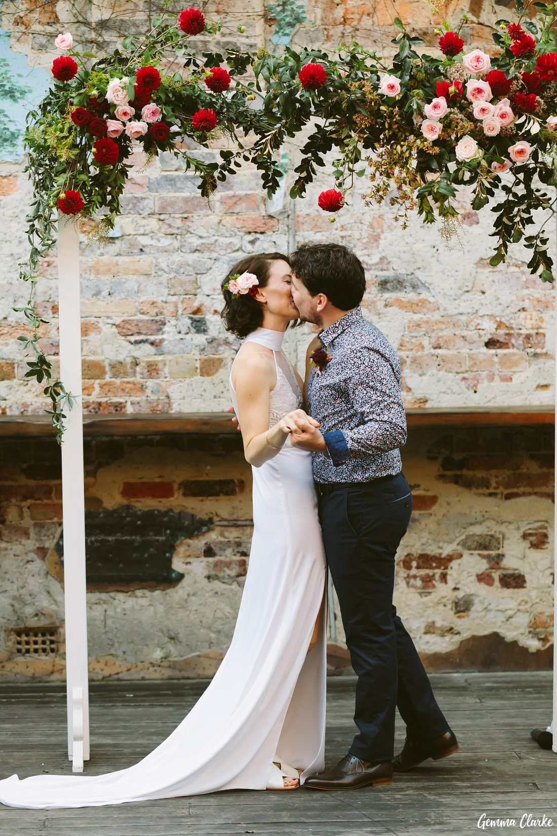 Bride and Groom's first kiss during the ceremony with a brick wall feature wall and red floral arbor at this sydney pub wedding