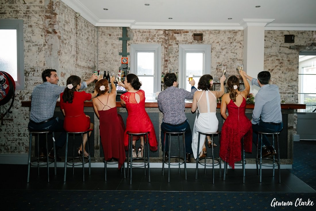 Bridal party lined up along the bar on stools with their backs showing and making a toast with each other at this Sydney Pub Wedding