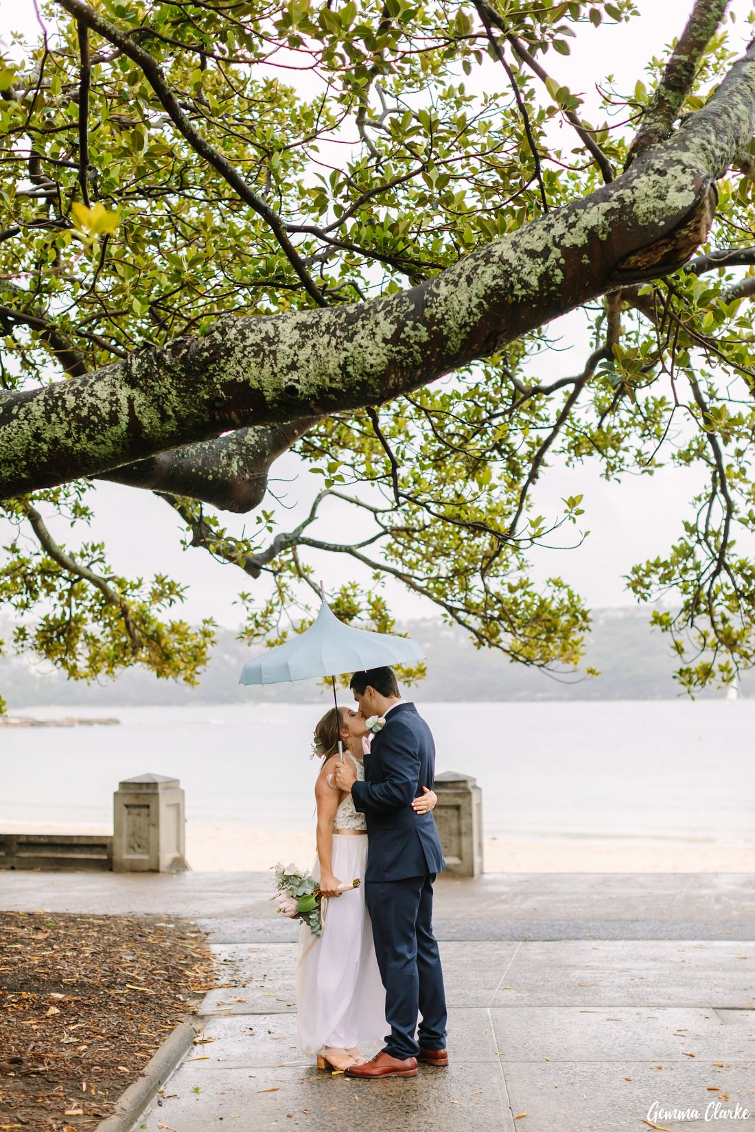 Bride and Groom snuggle under a big tree and blue umbrella on Balmoral Beach at this Sydney rainy day wedding