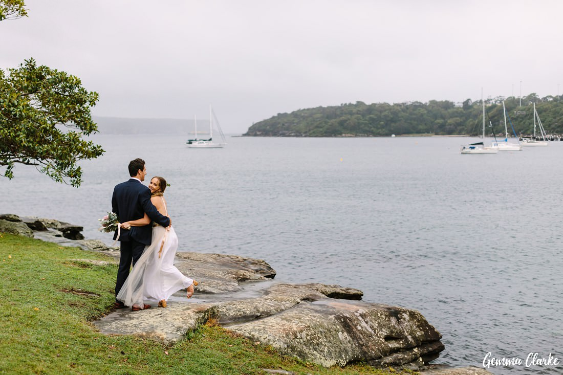 Bride and groom standing on some rocks overlooking the Balmoral area with boats in the background at this Sydney rainy day wedding