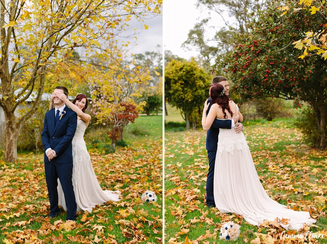 A first look session where the bride put her hands over the groom's face from behind and then revealed her and her outfit with smiles at this Autumn Southern Highlands Wedding