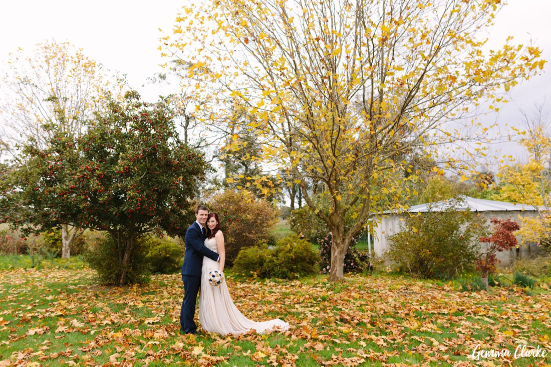 Stunning trees with falling leaves and yellow and red colours as the bride and groom embrace at this Autumn Southern Highlands Wedding