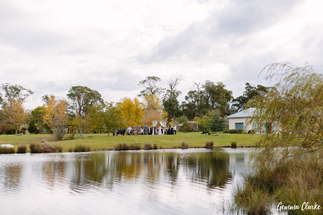 A view of the ceremony happening from across the lake and the beautiful reflections at this Autumn Aouthern Highlands Wedding